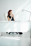 Redheaded woman in the workplace. Beautiful redheaded woman in the workplace with a cup of coffee Royalty Free Stock Image