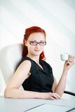 Redheaded woman in the workplace Royalty Free Stock Images