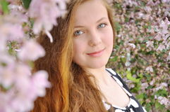 Redheaded young girl. A redheaded young girl is in a spring garden Stock Images