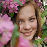 Redheaded young girl. A redheaded young girl is in a spring garden Stock Image