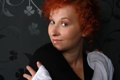 Redheaded young woman. In studio near black wallpaper Royalty Free Stock Photo