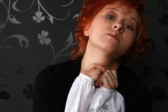 Redheaded young woman. In studio near black wallpaper Stock Images
