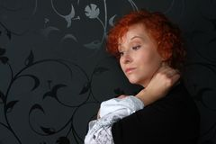 Redheaded young woman. In studio near black wallpaper Royalty Free Stock Images
