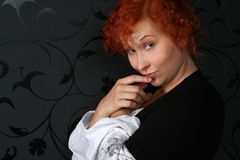 Redheaded young woman. In studio near black wallpaper Stock Image