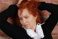 Redheaded young woman. In studio near brick wall Royalty Free Stock Photography