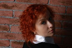 Redheaded young woman. In studio near brick wall Stock Images