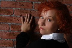 Redheaded young woman. In studio near brick wall Stock Image