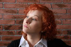 Redheaded young woman. In studio near brick wall Royalty Free Stock Photos