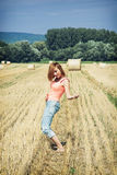 Redheaded young woman imitates guitar play at the field Stock Image