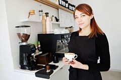 Redheaded young woman working in coffee shop prepearing a drink royalty free stock photos