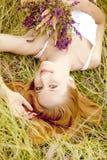 Redheadflicka på utomhus- med blommor. Royaltyfri Foto