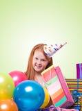 redheadflickan i partihatt med ballonger och gåvan boxas Arkivbild