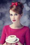 Redheadflickan med kaffe kuper. St. Valentin dag. Arkivbild