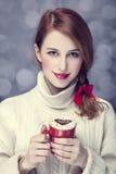 Redheadflickan med rött kaffe kuper. St. Valentindag Arkivbild