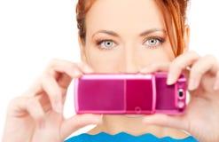 Redheadfrau, die Telefonkamera verwendet Lizenzfreie Stockfotografie