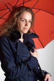 Redheadfrau unter rotem Regenschirm Stockbilder