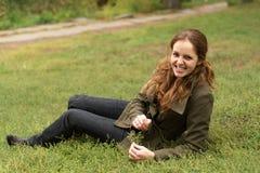 Redheadfrauenlüge auf dem Gras Lizenzfreies Stockfoto