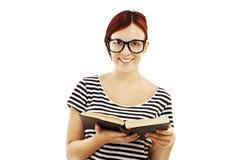 Redheadkvinna med exponeringsglas som läser en bok Arkivfoto