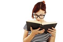 Redheadkvinna med exponeringsglas som läser en bok Royaltyfri Foto
