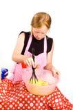 Redheadmädchen bildet Pfannkuchenteig Stockfoto
