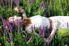 Redheadmädchen in den purpurroten Blumen. Lizenzfreies Stockfoto