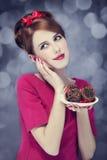 Redheadmädchen mit Kuchen für St.-Valentinstag. Stockfoto