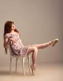 Redheadmädchen, das auf pointe Schuhen versucht Stockbild