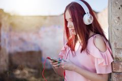 Redheads teenager girl using smartphone and headphones, listen to music on retro ruins wall stock photos