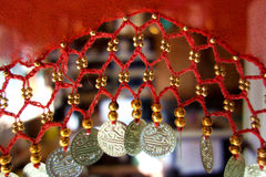 Red Indian Scarf with Coins. A Red Indian scarf with coin style beads dangling off as a fringe with a blurred background Stock Images