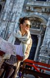 Smiling woman in Milan, Italy with map looking into distance Royalty Free Stock Image