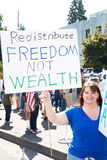 Redistribute freedom not wealth. Women holding a sign reading Redistribute Freedom not wealth at the state capital in Salem, Oregon Royalty Free Stock Photography