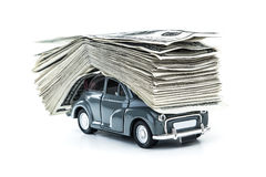 Сredit for car. Small decorative car model carries on itself a lot of cash isolated on white background, dollars of USA, credit for car concept Royalty Free Stock Photos