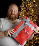 Redneck Gift Wrapping. Obese man wrapping a present with duct tape Royalty Free Stock Image