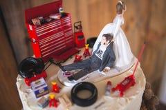 Redneckbröllopstårtatopper med mekanikerbrudgummen Arkivbild