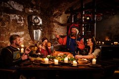 Średniowieczni ludzie jedzą i piją w antycznym grodowym kuchennym wnętrzu Zdjęcia Royalty Free
