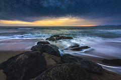 Redondo Beach Sunset. Long-exposure photograph of silky smooth water flowing around rock formations at sunset with dramatic clouds in the sky, Redondo Beach royalty free stock images