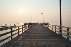 Fishing pier at sunset. Redondo Beach, WA, USA Aug. 3, 2017: Sun setting through smoke from distant fire bathes fishing pier in soft light at Redondo Beach Stock Photo
