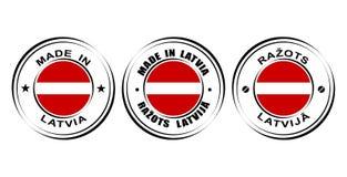 ` Redondo de la etiqueta hecho en el ` de Letonia con la bandera Fotografía de archivo