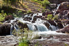Redrock Lake Falls. Powerful fast moving water from melting snow flows over red rocks and into Redrock Lake in Glacier National Park, Montana royalty free stock photos