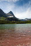 Redrock Lake and Mountains. Clear cold water over red rocks gradually deepens to light green and then reaches the far shore of lush green trees and grass at the stock photos