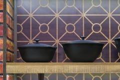 Redskap och husmanskostredskap Två nya järn- krukor med ett lock för att laga mat på en trähylla royaltyfri fotografi