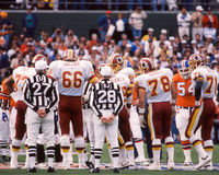 Redskins and Broncos Superbowl Coin Toss. Captains for the Broncos and Redskins watch the coin toss before the start of the Super Bowl. (Image taken from color royalty free stock photos