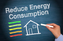 Reduce energy consumption. Text 'Reduce Energy Consumption' written in white on a black chalk board with an illustration of a house below and five colored bands stock images