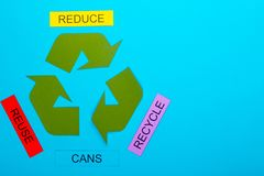 Reduce, Reuse & Recycle. Recycle concept showing the green recycle logo with reduce, reuse, recycle & cans on a blue background stock image