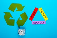 Reduce, Reuse & Recycle. Recycle concept showing the green recycle logo with reduce, reuse, recycle & foil on a blue background royalty free stock photos