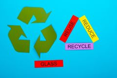 Reduce, Reuse & Recycle. Recycle concept showing the green recycle logo with reduce, reuse, recycle & glass on a blue background stock images