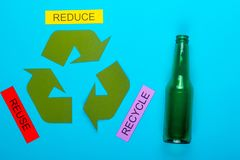 Reduce, Reuse & Recycle. Recycle concept showing the green recycle logo with reduce, reuse, recycle & glass on a blue background stock image