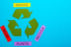 Reduce, Reuse & Recycle. Recycle concept showing the green recycle logo with reduce, reuse, recycle & plastic on a blue background royalty free stock photo