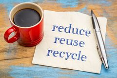 Reduce, reuse, recycle - conservation concept. Handwriting on a napkin with a cup of coffee Royalty Free Stock Photos