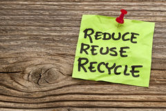 Reduce, reuse and recycle note. Reduce, reuse and recycle reminder note against grained wood - resource conservation concept Royalty Free Stock Images